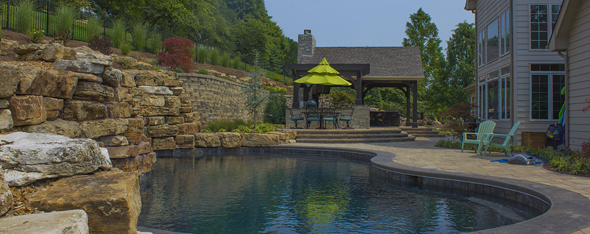 Backyard resort in St. Louis featuring an outdoor room, fireplace, outdoor kitchen and bar, and large pool with waterfalls.
